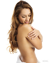 Topless woman with long brown hair looking back over her shoulder