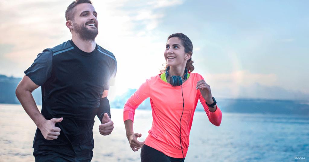 Man and woman jogging along the shore