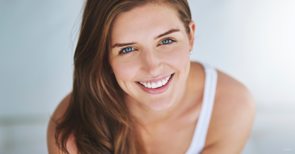 Smiling young woman with dark hair and blue eyes