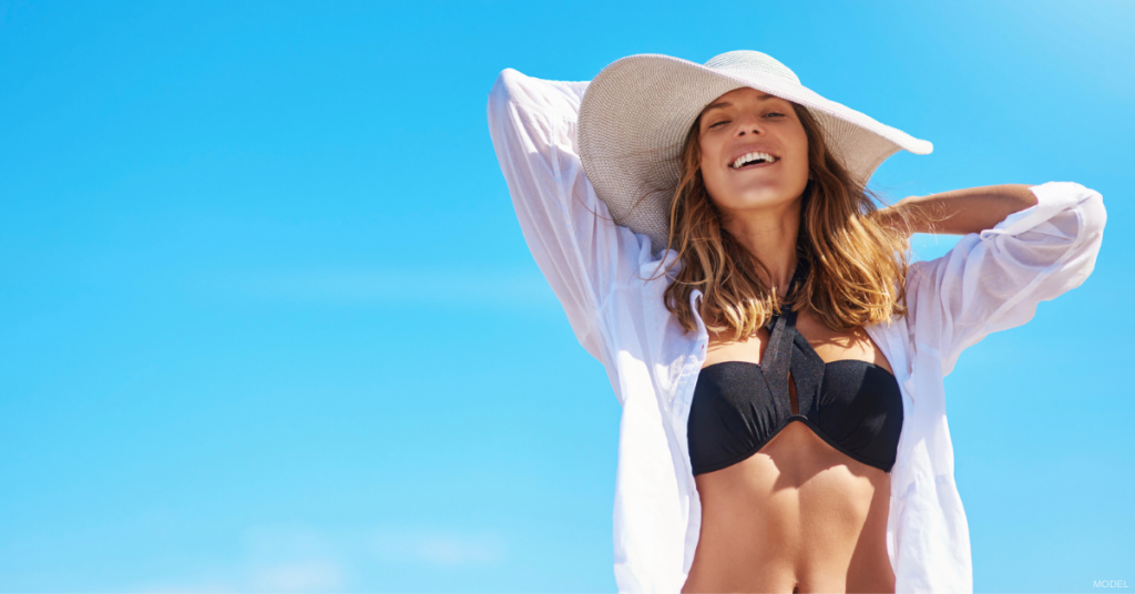 Beautiful woman smiling in bathing suit and sun hat