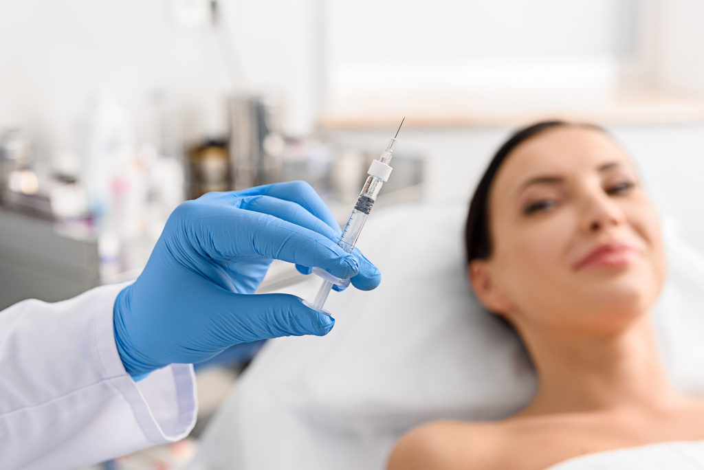 Doctor hand holding medical syringe while patient smiles in background